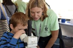 Young boy and woman at microscope