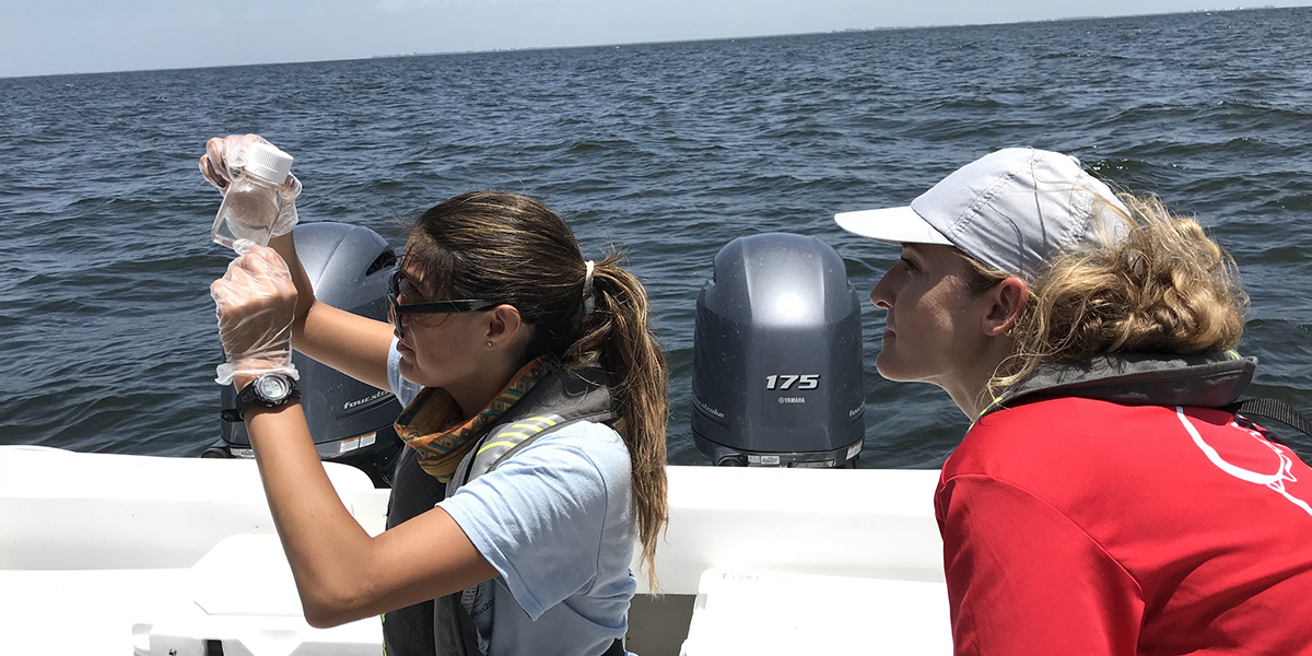 two women on boat looking at water sample